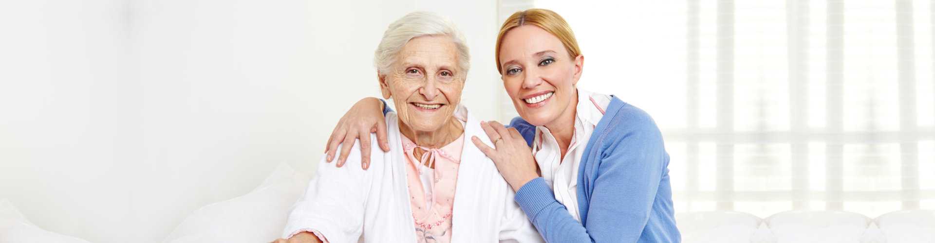 woman hugging senior woman in a white themed room
